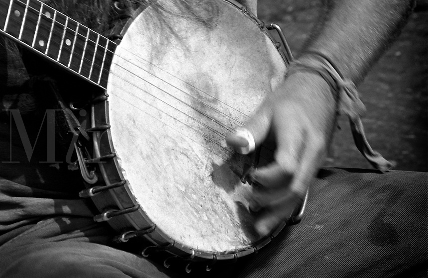 Black & white close up of hands strumming a banjo.