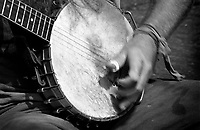 Black & white close up of hands strumming a banjo.