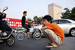 XIAN, CHINA -JUNE 4: An unidentified young man speaks on a mobile phone while sitting on the payment in central Xian, China. on June 4, 2007 in central Xian, China. The city has about 3,3 million inhabitants and is the capital of Shaanxi province in China. It was the eastern terminus for the Silk Road and the location for the Terracotta Army during the Qin Dynasty. Its history dates back more than 3,100 years. .(Photo by Per-Anders Pettersson)..