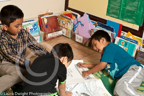 Education preschool 3-4 year olds group of three boys clustered around big book talking pointing out letters