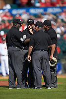 The umpires get together to discuss a call during the game between the Florida State Seminoles and the Louisville Cardinals in Game Eleven of the 2017 ACC Baseball Championship at Louisville Slugger Field on May 26, 2017 in Louisville, Kentucky. The Seminoles defeated the Cardinals 6-2. (Brian Westerholt/Four Seam Images)