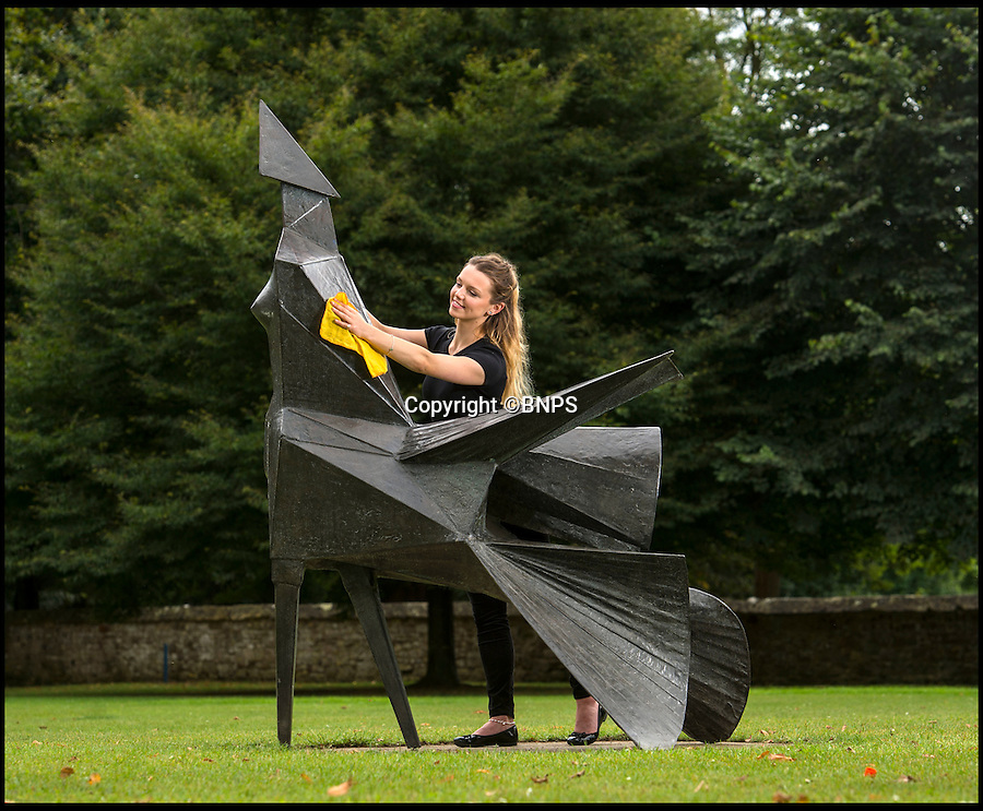 BNPS.co.uk (01202 558833)<br /> Pic: PhilYeomans/BNPS<br /> <br /> Final polish - as a new bronze sculpture is unveiled at Salisbury Cathedral yesterday...<br /> <br /> Artist Lynn Chadwick's 'Walking Woman' sculpture was installed on the west lawn of Salisbury Cathedral yesterday.<br /> <br /> The monumental walking woman is considered one of the great achievements of Chadwicks career, a strong confident figure, with an immense cloak billowing behind as she marches towards the cathedral.<br /> <br /> The cathedral is renowned for its promotion of the art's in and around the 800 year old building that boasts Britains tallest spire and welcomes over 300,00 visitors from all over the world each year.