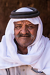 A Bedouin man wearing a keffiyeh (head scarf) and agal (rope headband) in Petra in the Hashemite Kingdom of Jordan.  Petra Archeological Park is a Jordanian National Park and a UNESCO World Heritage Site.