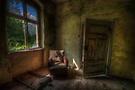 An old house in Frankfurt Oder with old chair next to window and open door