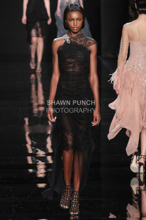 "Model walks runway in a black lace asymmetric dress with embroidered detail from the Reem Acra Fall 2016 ""The Secret World of The Femme Fatale"" collection, at NYFW: The Shows Fall 2016, during New York Fashion Week Fall 2016."