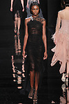 """Model walks runway in a black lace asymmetric dress with embroidered detail from the Reem Acra Fall 2016 """"The Secret World of The Femme Fatale"""" collection, at NYFW: The Shows Fall 2016, during New York Fashion Week Fall 2016."""