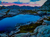 A small tarn or  pond high in the Weminuche Wilderness Area in southwest Colorado reflects the first light of morning.