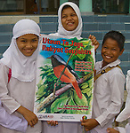 """Zakiah's pride campaign visit with school kids in Lok Nga village. Pride campaign poster reads """"When the forest is protected, people prosper"""". The chosen mascot is the Rufous-tailed Shama (Copsychus pyrrhopygus)."""