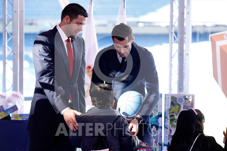 Real Madrid´s Felipe Reyes (L) and Rudy Fernandez attend the presentation of No kids without a present on Christmas campaign at Bernabeu stadium in Madrid, Spain. December 16, 2013. (ALTERPHOTOS/Victor Blanco)