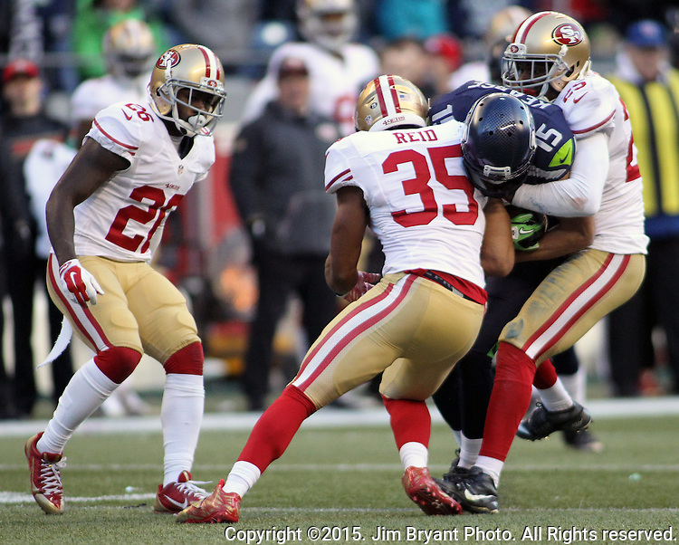 Seattle Seahawks wide receiver Jermaine Kearse (15) protects the ball while getting hit by San Francisco 49ers defensive back Jimmie Ward (25) and safety Eric Reid (35) at CenturyLink Field in Seattle, Washington on November 22, 2015.  The Seahawks beat the 49ers 29-13.   ©2015. Jim Bryant Photo. All RIghts Reserved.