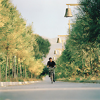 Local man riding bicycle, Silk Route, Dunhuang, Jiuquan, Gansu Province, China.