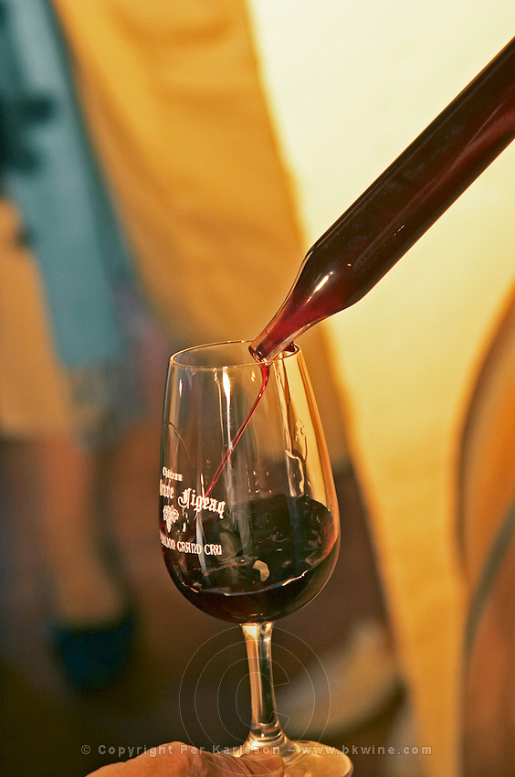 A wine sampling pipette taking a sample from a barrel and pouring in a glass - Chateau La Grave Figeac, Saint Emilion, Bordeaux