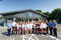 Lewis Eady (C) with schoolmates from year 6 of ysgol Rhys Pritchard and members of Co op staff, cuts the ribbon.