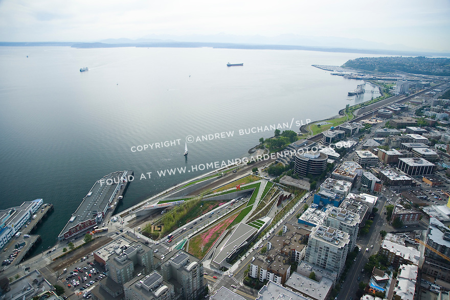 Aerial view looking northwest along the Seattle waterfront at the Olympic Sculpture Park.  Elliott Bay is behind and Elliott Avenue, a major thoroughfare, runs underneath the center of the park.
