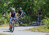 First lady Michelle Obama, left, United States President Barack Obama, center, and daughter Malia Obama, right, ride their bicycles on the Manuel F. Correllus State Forest bike path outside of West Tisbury, Massachusetts on Friday, August 15,  2014 during their summer vacation.<br /> Credit: Rick Friedman / Pool via CNP