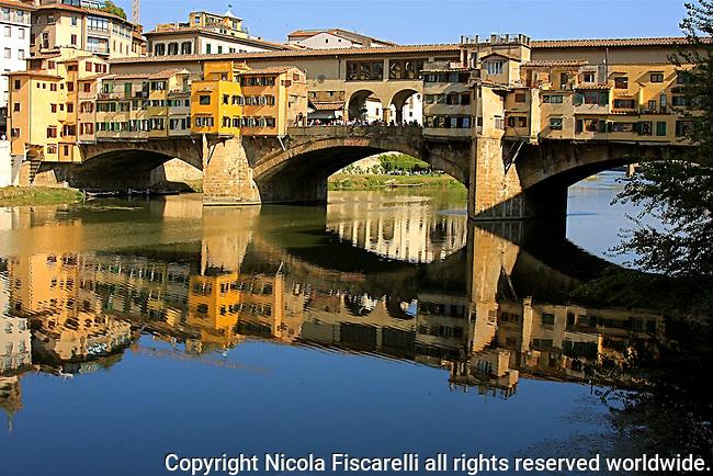 The beautiful mirror reflection of the Florentine bridge , thePonte Vecchio (Old Bridge), in the  river Arno .