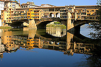 The beautiful mirror reflection of the Florentine bridge , thePonte Vecchio (Old Bridge), in the  river Arno .
