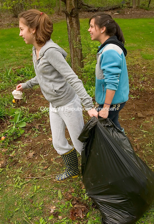 WOODBURY, CT- 04 MAY 2008 --050408JS07-Lauren Socia, 12 and Sami Albert, 11, both of Southbury, try to haul a bag of debris to the curb after helping clean up at the Spruce Bank Farm housing complex in Woodbury on Sunday. Sixth-grade students from the B'nai Israel religious school in Southbury were sprucing up the complex as part of Mitzvah Day, a day of good deeds. <br /> Jim Shannon / Republican-American