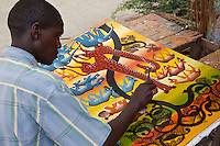 Zanzibar, Tanzania.  Tingatinga painter at work in Stone Town.