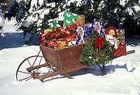 Antique wheelbarrow sitting in the snow filled with presents, dolls and gifts decorated with a wreath at grandmothers house