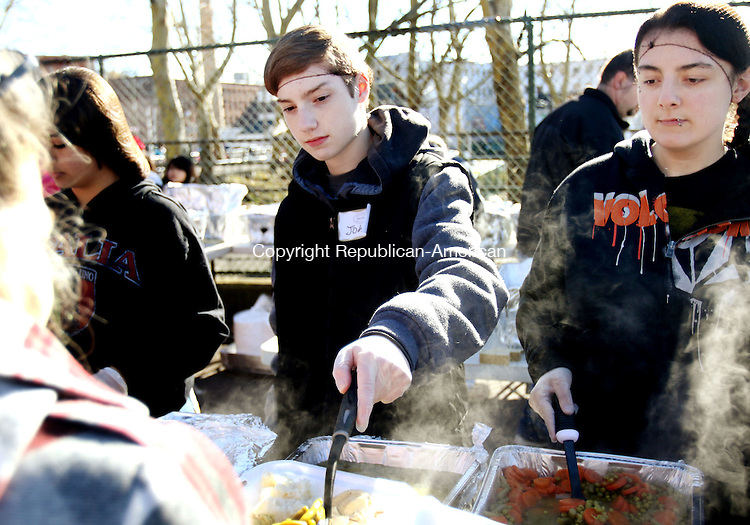 WATERBURY CT. 21 November 2015-112115SV03-From left, John Sarandrea, 16, of Naugatuck and Lauren Iraci, 16, of Prospect serve Thanksgiving Dinner while volunteering with Christ Church of Wolcott in Martin Luther King Park in Waterbury Saturday. <br /> Steven Valenti Republican-American