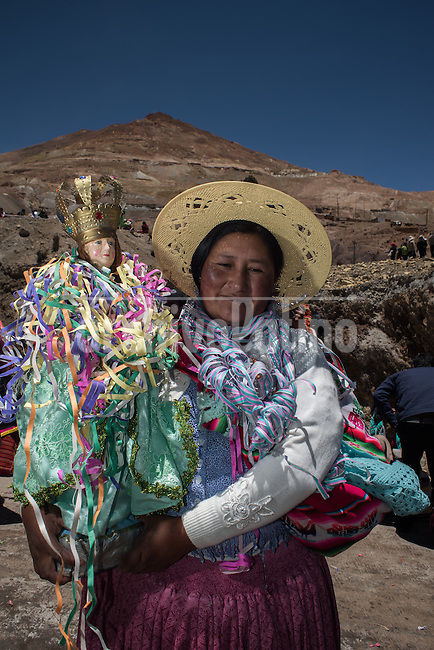 "A woman carrys their Tata Kajchu (Saint of the mine) to the Cathedral to be blessed, in this case a statue of the Virgin Mary. Potosi, Bolivia. 23 January 2016. With this blessing, they begin the festivities of the Miners Carnival./ Una mujer lleva su Tata Kajchu (santo de la mina) a la catedral para su correspondiente bendición, en este caso una estatua de la Virgen María. Potosí, Bolivia. Enero 23 de 2016. Con esta bendicion empiezan las fiestas del Carnaval Minero. The customs and beliefs of Andean people are a hybrid of catholic religion and old beliefs. One of its highest expressions is within the Bolivian mining culture that worships the Pacha Mama (Mother Earth), the Celestial Divinity personified in the Catholic God and ""El Tio"" of the mine (Satan). To the latter, who rules the underworld, they make offerings with sacrifices of llamas inside the mines to ask for protection in the depths of the mountain and abundant mineral."