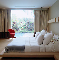 A red Verner Panton Cone chair sits in the corner of the bedroom infront of the picture window overlooking the outdoor pool