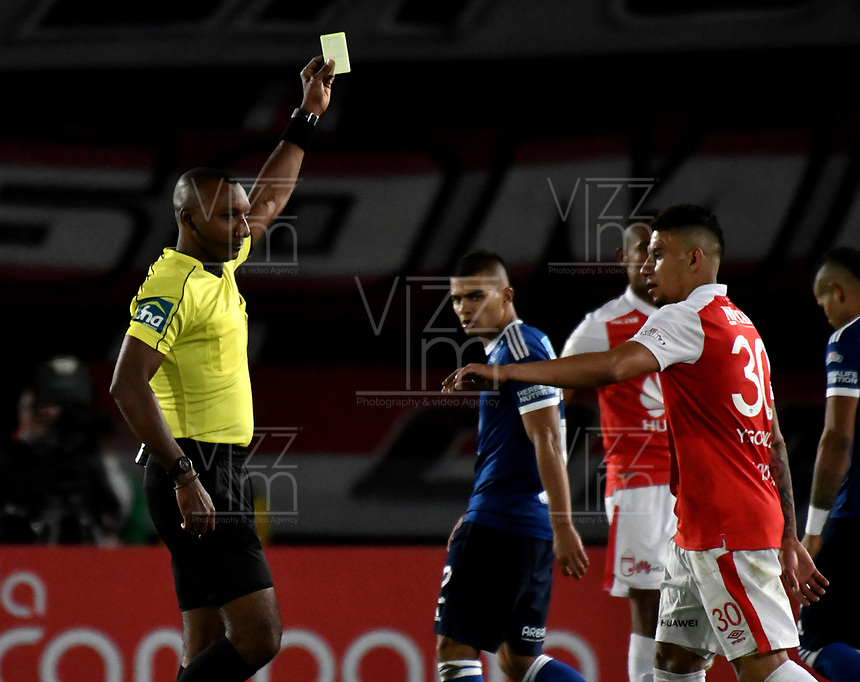 BOGOTÁ - COLOMBIA, 06-05-2018: Gustavo Murillo (Izq.), arbitro, muestra tarjeta amarilla a Yeison Gordillo (Der.), jugador de Independiente Santa Fe, durante partido de la fecha 19 entre Independiente Santa Fe y Millonarios, por la Liga Aguila I 2018, en el estadio Nemesio Camacho El Campin de la ciudad de Bogota. / Gustavo Murillo (L), referee, shows yellow card to Yeison Gordillo (R) player of Independiente Santa Fe, during a match of the 19th date between Independiente Santa Fe and Millonarios, for the Liga Aguila I 2018 at the Nemesio Camacho El Campin Stadium in Bogota city, Photo: VizzorImage / Luis Ramírez / Staff.