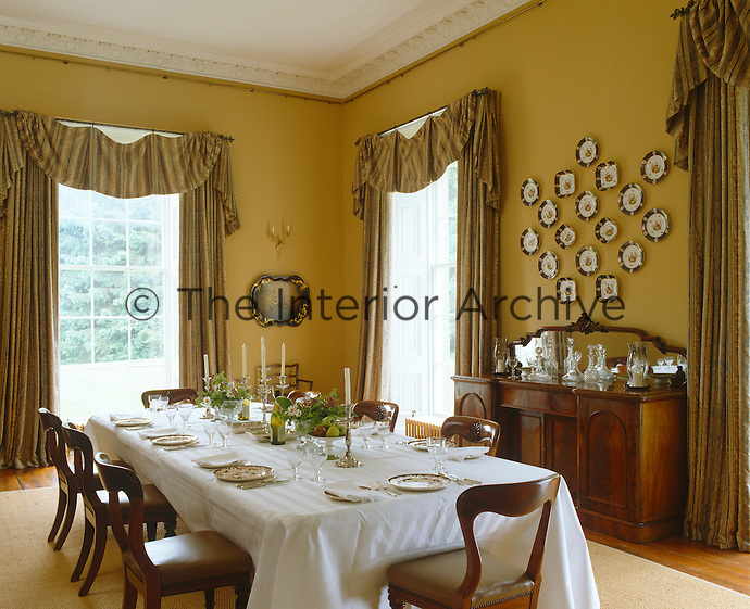 The dining room curtains are made of an Italianate brocade and the pelmets designed to look 'once grand'