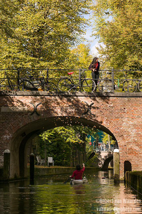 A woman kayaks under a bridge on the canals of Utrecht, the Netherlands.