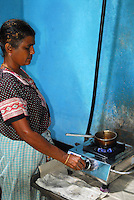 INDIA Karnataka Taccode, woman cooks with biogas from small biogas plant at farm, save of fire woods / INDIEN Frau auf einen Bauernhof kocht in der Kueche mit Biogas von einer kleinen Biogasanlage