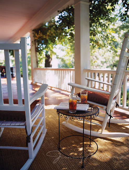 Sun shines onto a rocking chair front porch with two empty seats, each with an iced tea
