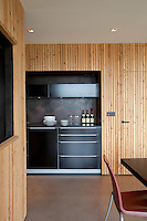 The kitchen/dining area features a series of black kitchen units framed by pine clad walls