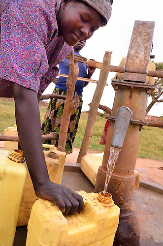 In northern Uganda, women from remote villages access safe drinking water from dozens of new wells.  The bore holes are a component of U.S. AID and Winrock International's  $30 million NUDEIL project to help revitalize and improve basic life in the impoverished, war-torn region.  The new wells reduce long distances most residents travel for their water.