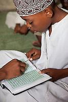 Zanzibar, Tanzania.  Young Boy in Madrassa (Koranic School) Practicing Reading the Koran.
