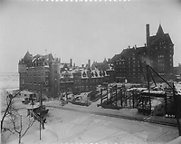 Construction of the side wing of the Chateau Frontenac, photograph, 1921, from the Archives of the Chateau Frontenac, Quebec City, Quebec, Canada. The Chateau Frontenac opened in 1893 and was designed by Bruce Price as a chateau style hotel for the Canadian Pacific Railway company or CPR. It was extended in 1924 by William Sutherland Maxwell. The building is now a hotel, the Fairmont Le Chateau Frontenac, and is listed as a National Historic Site of Canada. The Historic District of Old Quebec is listed as a UNESCO World Heritage Site. Copyright Archives Chateau Frontenac / Manuel Cohen