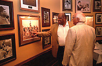 Former Green Bay Packers defensive end Willie Davis shows former Packers guard Fuzzy Thurston a photo in which Packers defensive back Herb Adderley is jumping very high in an effort to block a kick. Davis and Thurston were attending the Lombardi players reunion at the Lombardi Steakhouse in Appleton, Wisconsin in September of 2001.