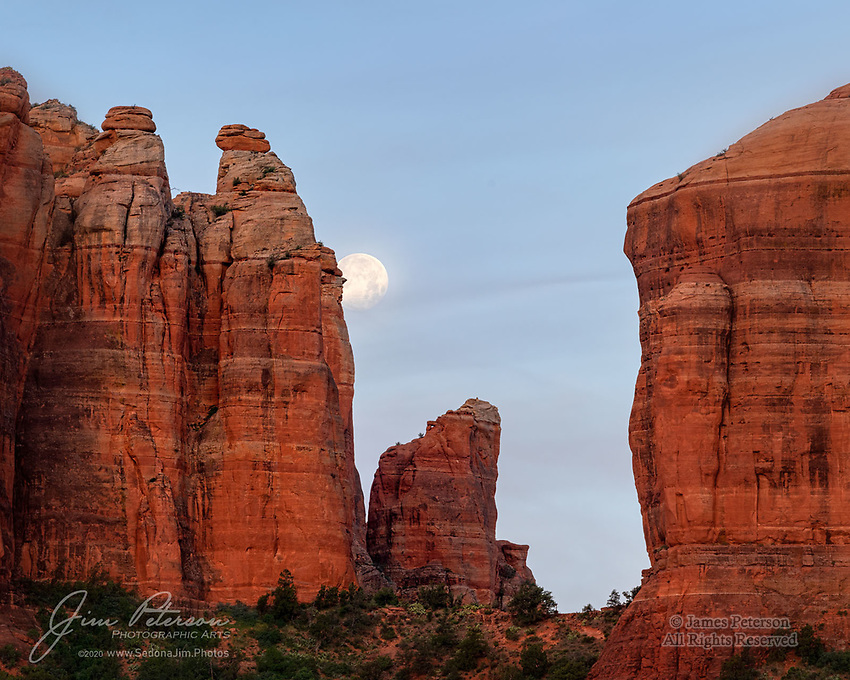 """Moonset over Cathedral Rock.  This was the last of the three """"supermoons"""" of 2020, as seen just before sunrise on the day (May 8) after the full moon.  It was captured from atop a ridge overlooking the Templeton Trail in the Coconino National Forest, just south of Sedona.<br /> <br /> I thought at first that the thin clouds might ruin this photo, but I decided eventually that they actually add some nice character to the sky.  The glow of dawn above the eastern horizon added a nice bit of warmth to the red sandstone.<br /> <br /> Image ©2020 James D. Peterson"""