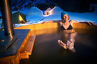 A woman sits in a hot tub at her yurt camp in Kyrgyzstan