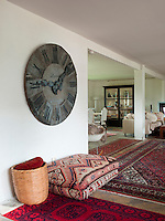 A large kilim pouffe and an antique French clock mark the entrance to the living/dining area of the farmhouse