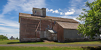 The rough, sawed timber framed J. C. Barren Flour Mill stands three and one-half stories in height in the northern portion of the small farming community of Oakesdale. the flour mill built by J. G. Porter during the late summer and autumn of 1890. With the completion of a Northern Pacific Railroad spur track to the mill building in early December, the mill was running and flour was being produced on contract to local farmers and merchants. The mill, owned by the Joseph Barron family for almost a century and now owned by MaryJane Butters, is the only intact flour mill remaining on the Palouse.