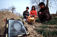 QSFeature03AIDS020 20020212 DONGGUAN, CHINA: .7 year old Wang Keyun (L)  and 13 year old Wang Jiashu (C) paying respect to their mother, who died of AIDS last year, in Dongguan village, Henan Province, China 12 February 2002. Their father Wang Liang (R) also has the disease. Over 700,000 peasant farmers in Henan Province have contracted the HIV virus when they participated in the unregulated blood selling/buying boom of the early and mid nineties.