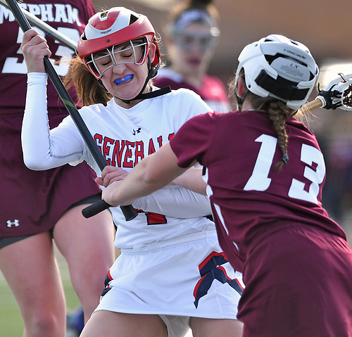 Marisa Misuraca #4 of MacArthur, left, gets checked by Amanda Amalfitano #13 of Mepham during a Nassau County varsity girls lacrosse game against Mepham at MacArthur High School on Monday, March 20, 2017. MacArthur won by a score of 13-6.