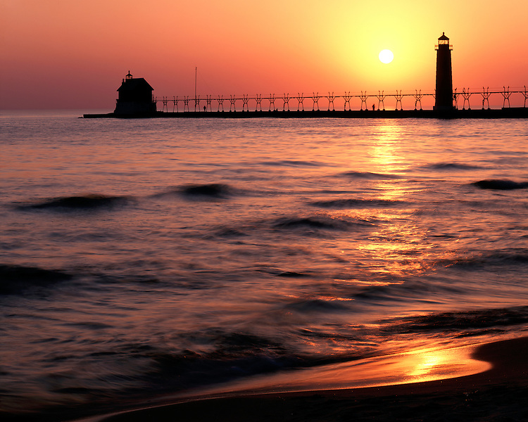 Sunset light on the Grand Haven Lighthouse on Lake Michigan; Grand Haven State Park, Michigan