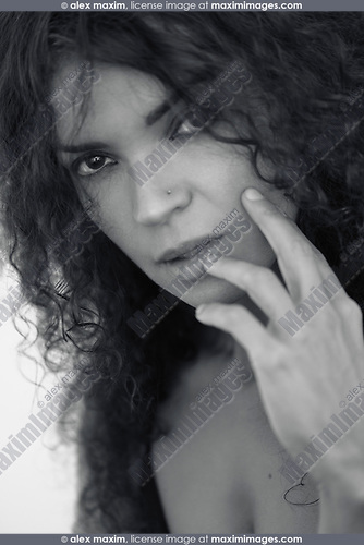 Closeup black and white beauty portrait of a young caucasian brunette woman with a deep and piercing expressive look on her beautiful face with long curly dark hair