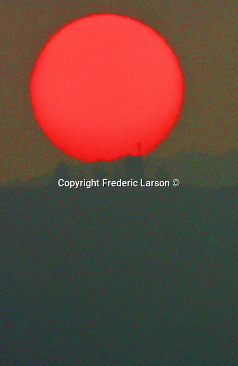 A huge red ball of sun was photographed with a large telephoto lens was imminent over the eastern horizon one morning in San Francisco, California