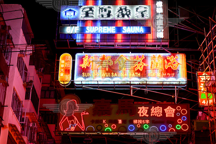 Neon signs, advertising sauna services and karaoke clubs, in the backstreets of the Mongkok District.
