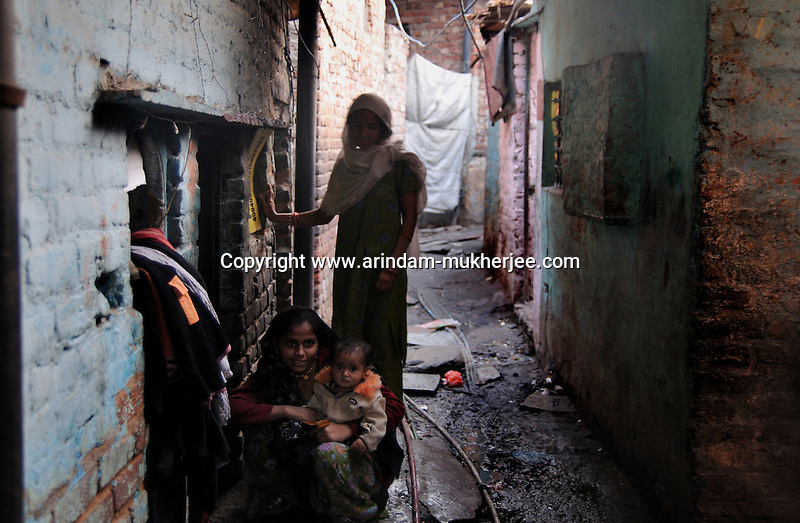 A lady sits with her child  in front of his house at Katputly colony in New Delhi, India. 17.11.2009. Kathputly colony is a slum area in West Delhi. This slum seems like any other slum areas of modern India with dysfunctional electricity, non existing sanitation and poverty. As a part of Delhi, this is also ailed with water crisis. Large families live their lives crammed together in a single room with all the odds which complement poverty. One thing which differentiates this slum with any other is the people living in the colony. Nearly everybody in this slum is a traditional performing artist; and they have been migrating to this area for last 50 years from different parts of the country for a better livelihood. They are magicians, acrobats, jugglers, puppeteers, dancers and musicians. These artistes perform in star rated hotels, marriage ceremonies of the richer section, functions, and festivities all around the country and the world. Most of the artisans I met here, have performed in Europe and America but such opportunities are rare to come by. They struggle to keep their art form alive. They say that they don't get any help or support from the government for their basic needs and for the well being of the Kathputly colony -  though they have uphold the prestige of the country internationally. Polluted air, dirty alleys smelling of urine, colourful dress and sound of music characterise Kathputly colony, which is the one of its kind in India. Arindam Mukherjee