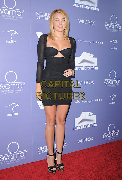 Miley Cyrus.Australians in Film 8th Annual Breakthrough Awards held at The Hotel Intercontinental in Century City, California, USA..June 27th, 2012  .full length black dress cut out away sheer sleeves cleavage ankle strap open toe platform shoes hand on hip                                                            .CAP/RKE/DVS.©DVS/RockinExposures/Capital Pictures.