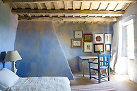 A rustic blue bedroom with terracotta tiled floor and beamed wood ceiling. The room is simply furnished with a bed with coarse linen, a painted table and chair focus the attention on a small gallery of artworks and the curtain is made from men's shirting material.